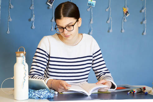 Portrait of girl sitting at desk with school book looking at digital tablet - LVF08763