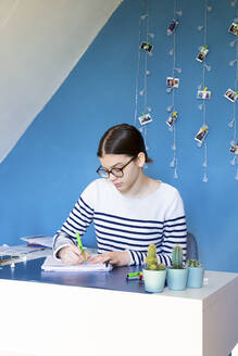 Portrait of girl sitting at desk at home doing homework - LVF08766