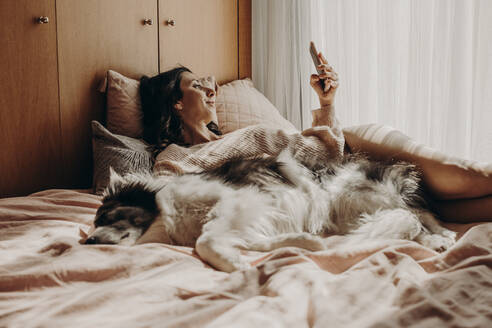 Woman relaxing with her dog on bed looking at smartphone - GMLF00003