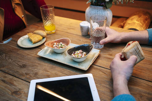 Two people sitting in restaurant, eating and drinling, with digital tablet on table - DGOF00768