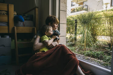 Mother and little son sitting on the floor at home looking out of window - MFF05411