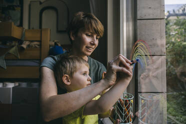 Mother and little son drawing rainbow on window at home - MFF05414