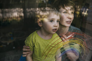 Portrait of mother and her little son looking out of window with drawn rainbow - MFF05417