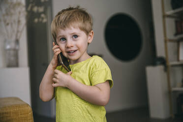 Portrait of smiling little boy on the phone at home - MFF05420