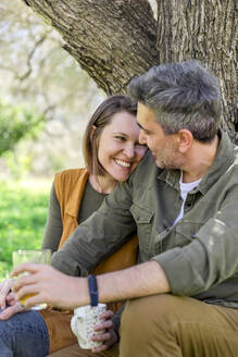 Happy couple sitting at a tree in the countryside - VSMF00021