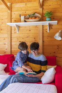 Mother and daughter reading a book on couch in a wooden cabin - VSMF00033