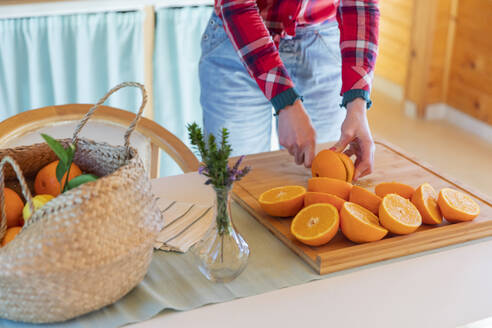 Close-up of woman slicing oranges in a wooden cabin - VSMF00069