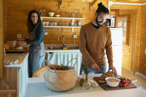 Young man with girlfriend in a wooden cabin cutting bread - VSMF00084