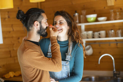 Happy young couple playing with a cherry tomato in a wooden cabin - VSMF00087