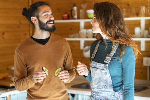 Young couple with avocados in a wooden cabin - VSMF00090