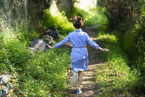 Girl running on a rural path, rear view - VSMF00150