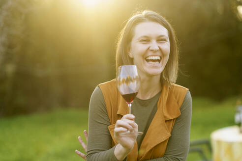 Happy woman drinking red wine in the countryside - VSMF00168