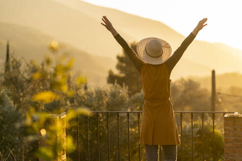 Woman enjoying the view of the sunset in the countryside raising arms, Orgiva, Andalusia, Spain - VSMF00174