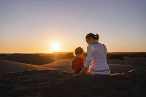 Mother and daughter sitting in sand dunes at sunset, Gran Canaria, Spain - DIGF09541