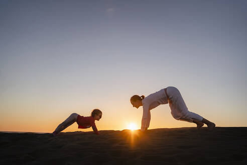 Mother and daughter practicing yoga in sand dunes at sunset, Gran Canaria, Spain - DIGF09547