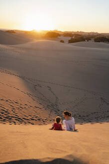 Mother and daughter relaxing in sand dunes at sunset, Gran Canaria, Spain - DIGF09550
