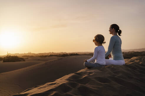 Mother and daughter practicing yoga in sand dunes at sunset, Gran Canaria, Spain - DIGF09601