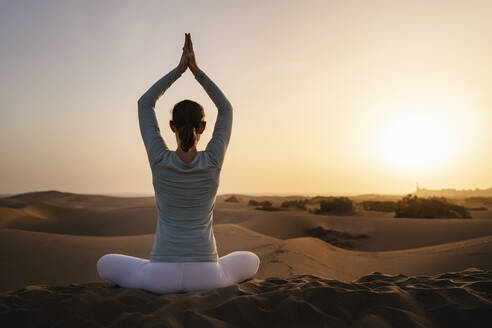 Woman practicing yoga in sand dunes at sunset, Gran Canaria, Spain - DIGF09604