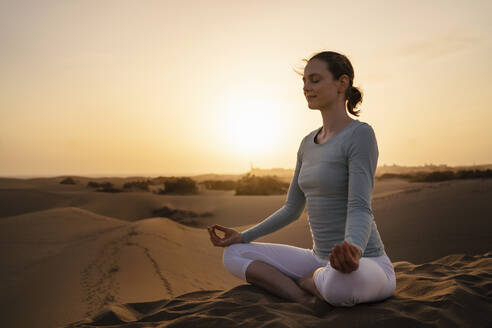 Woman practicing yoga in sand dunes at sunset, Gran Canaria, Spain - DIGF09610