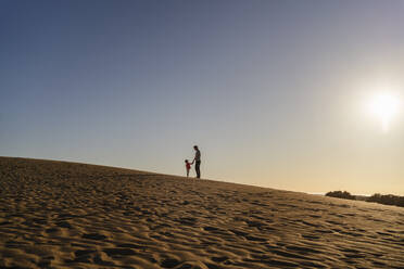 Father and daughter in sand dunes at sunset, Gran Canaria, Spain - DIGF09619