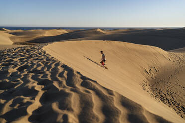 Father and daughter walking up sand dune, Gran Canaria, Spain - DIGF09622