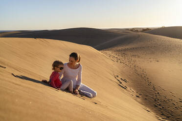 Mother and daughter sitting in sand dunes, Gran Canaria, Spain - DIGF09625