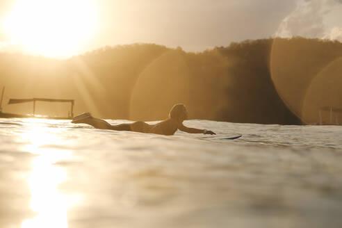 Female surfer in the ocean at sunset - CAVF79005