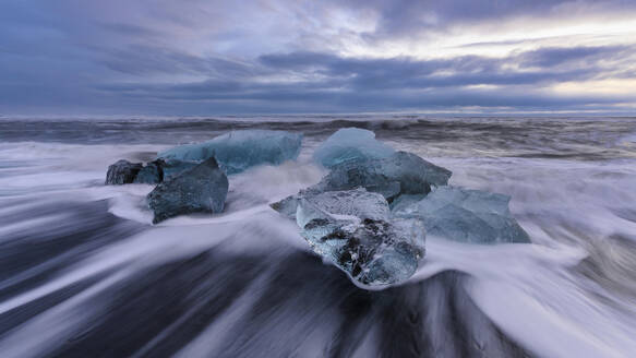 Iceland, Ice chunks lying at shore of Jokulsarlon at dusk - TOVF00167