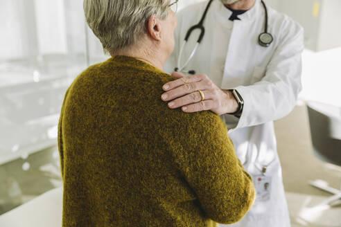 Doctor holding shoulder of senior patient in his practice - MFF05424