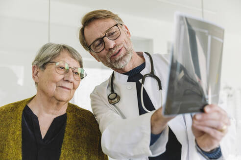 Doctor discussing x-ray image with senior patient - MFF05436