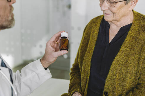 Doctor recommending pills in bottle to senior patient - MFF05445