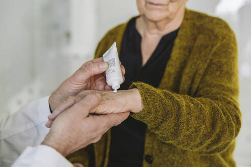 Doctor putting ointment on hand of senior patient - MFF05448