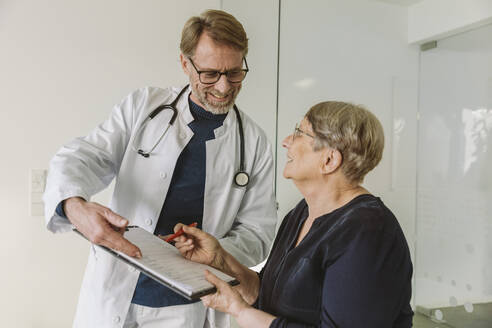 Doctor helping senior patient filling out document - MFF05454