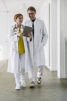 Two doctors waking along hallway using tablet - MFF05469
