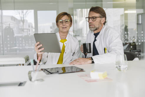 Two doctors sitting at desk using tablet - MFF05490