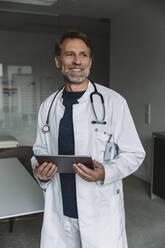 Portrait of smiling doctor holding tablet - MFF05550