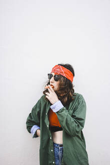 Portrait of young woman wearing headband and sunglasses smoking carrot - FVSF00073