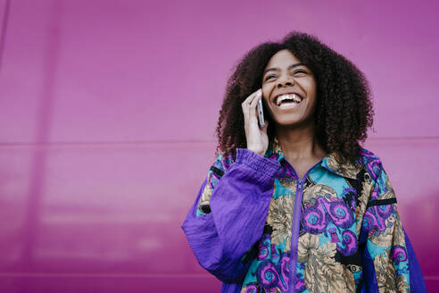 Smiling woman talking on the phone, pink wall in the background - TCEF00472