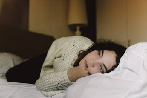 Portrait of pensive girl lying on bed looking at distance - ERRF03391
