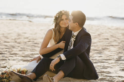 Happy bridal couple sitting at the beach - LHPF01257