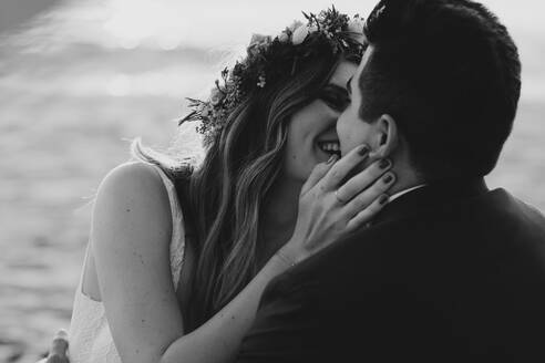 Happy bridal couple kissing each other at the beach, black and white - LHPF01263