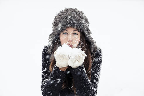 Portrait of young woman blowing snow - WFF00296