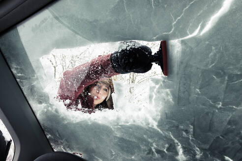 Portrait of young woman cleaning snow from car's windscreen - WFF00311