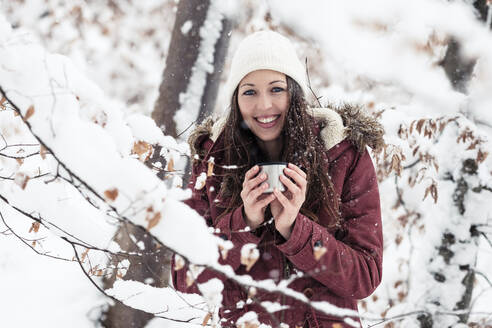 Portrait of happy young woman with hot beverage in winter - WFF00314