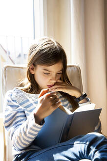 Portrait of girl sitting on armchair reading a book - LVF08777