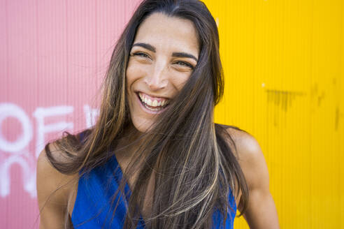 Young smiling woman in front of pink and yellow wall - DAMF00327