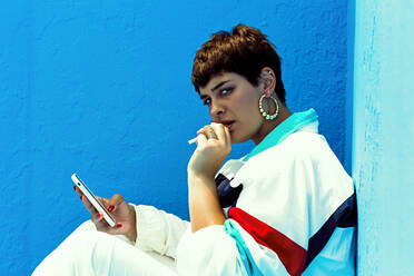 Woman wearing swag style smoking and checking her smartphone - ERRF03405