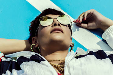 Portrait of woman wearing mirrored sunglasses and lying on ground - ERRF03411
