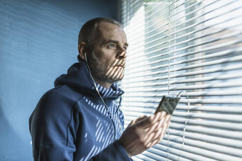 Pensive man with smartphone and earbuds looking out of venetian blind window - MCVF00279