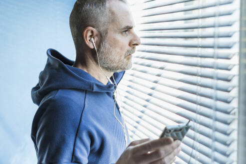 Pensive man with smartphone and earbuds looking out of venetian blind window - MCVF00282